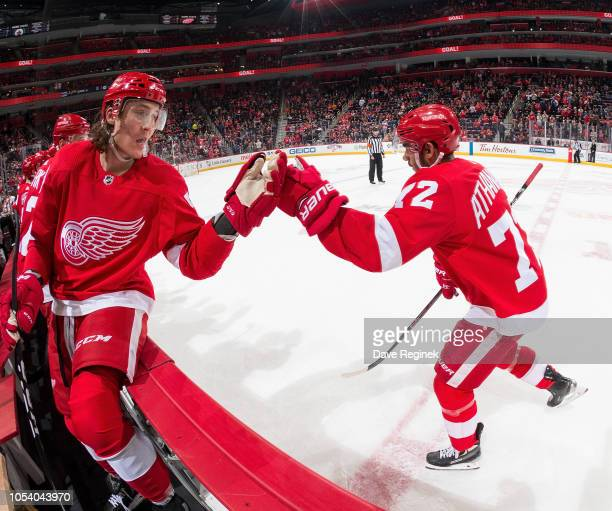 Andreas Athanasiou of the Detroit Red Wings pounds gloves with teammate Tyler Bertuzzi following his first period goal during an NHL game against the...