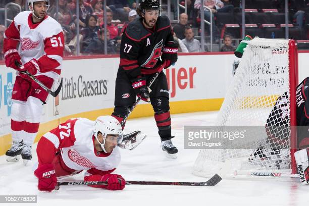 Andreas Athanasiou of the Detroit Red Wings reaches around the net to shoot the puck in front of Justin Faulk of the Carolina Hurricanes during an...
