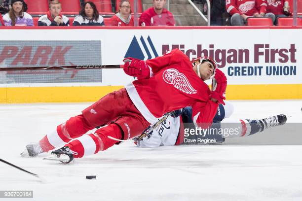 Andreas Athanasiou of the Detroit Red Wings reacts to getting hit with the stick of Travis Boyd of the Washington Capitals during an NHL game at...