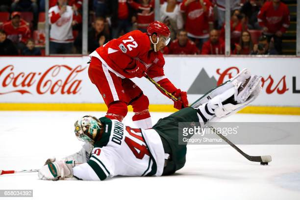 Andreas Athanasiou of the Detroit Red Wings scores in overtime past Devan Dubnyk of the Minnesota Wild for a 32 win at Joe Louis Arena on March 26...