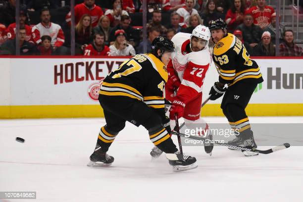 Andreas Athanasiou of the Detroit Red Wings shoots past Torey Krug of the Boston Bruins to score the game winning overtime goal to defeat the Boston...