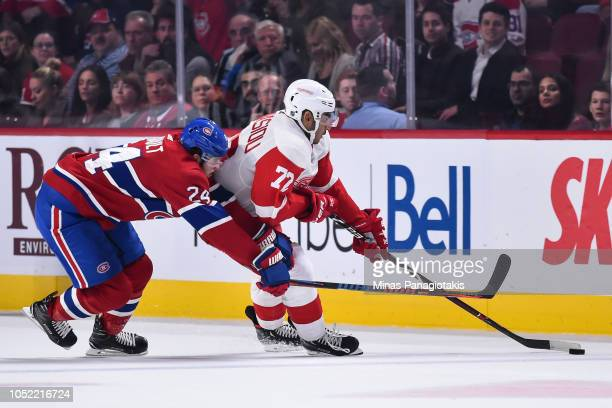 Andreas Athanasiou of the Detroit Red Wings skates the puck against Phillip Danault of the Montreal Canadiens during the NHL game at the Bell Centre...