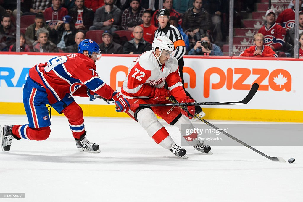 Andreas Athanasiou #72 of the Detroit Red Wings skates the puck against Andrei Markov #79 of the Montreal Canadiens during the NHL game at the Bell Centre on March 29, 2016 in Montreal, Quebec, Canada. The Montreal Canadiens defeated the Detroit Red Wings 4-3.