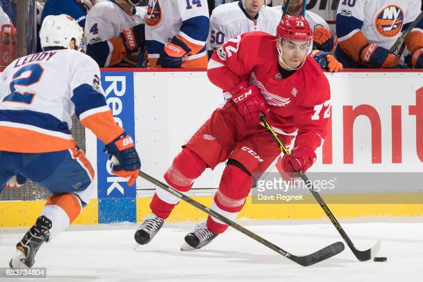 Andreas Athanasiou of the Detroit Red Wings skates up ice with the puck in front of Nick Leddy of the New York Islanders during an NHL game at Joe...