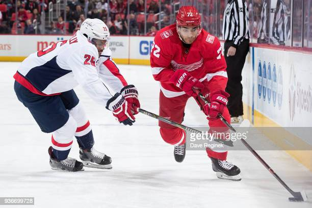 Andreas Athanasiou of the Detroit Red Wings skates with the puck along the boards as Devante SmithPelly of the Washington Capitals reaches for the...