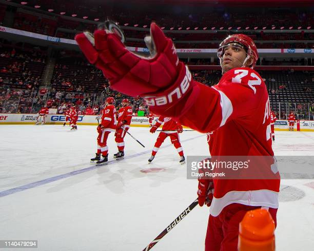 Andreas Athanasiou of the Detroit Red Wings tosses a puck to a fan in warmups prior to an during an NHL game against the Pittsburgh Penguins at...