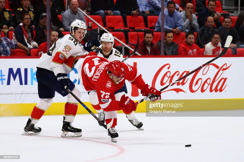 Andreas Athanasiou #72 of the Detroit Red Wings tries to avoid the stick of Jared McCann #90 of the Florida Panthers during the third period at Little Caesars Arena on December 11, 2017 in Detroit, Michigan. Florida won the game 2-1 in overtime.