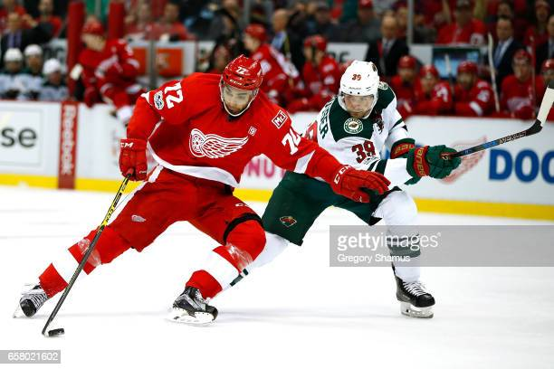 Andreas Athanasiou of the Detroit Red Wings tries to control the puck while being defended by Nate Prosser of the Minnesota Wild during the second...