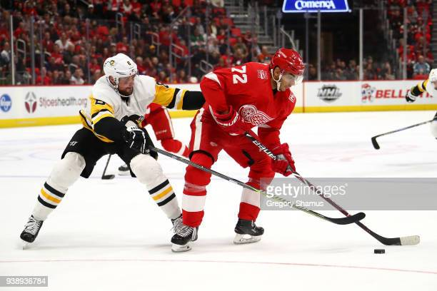 Andreas Athanasiou of the Detroit Red Wings tries to control the puck in front of Brian Dumoulin of the Pittsburgh Penguins during the second period...