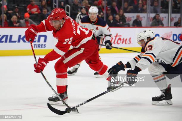 Andreas Athanasiou of the Detroit Red Wings tries to get a shot off around the stick of Matt Benning of the Edmonton Oilers during the third period...