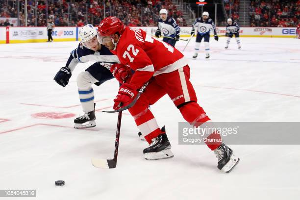 Andreas Athanasiou of the Detroit Red Wings tries to get around Jacob Trouba of the Winnipeg Jets during the second period at Little Caesars Arena on...
