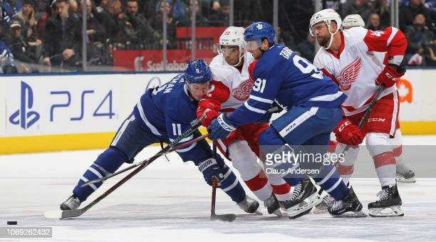 Andreas Athanasiou of the Detroit Red Wings tries to squeeze between Zach Hyman and John Tavares of the Toronto Maple Leafs during an NHL game at...