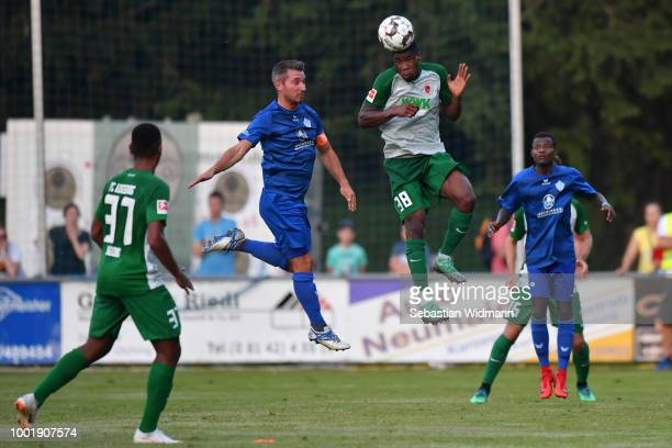 Andreas Bartl of Olching and Kevin Danso of Augsburg jump for a header during the preseason friendly match between SC Olching and FC Augsburg on July...
