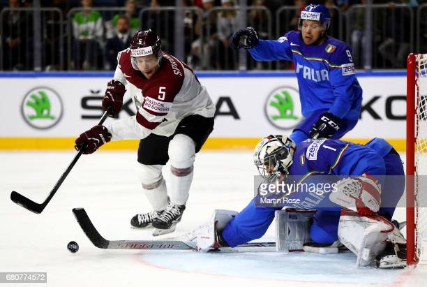Andreas Bernard goaltender of Italy makes a save on Janis Sprukts of Latvia during the 2017 IIHF Ice Hockey World Championship game between Italy and...