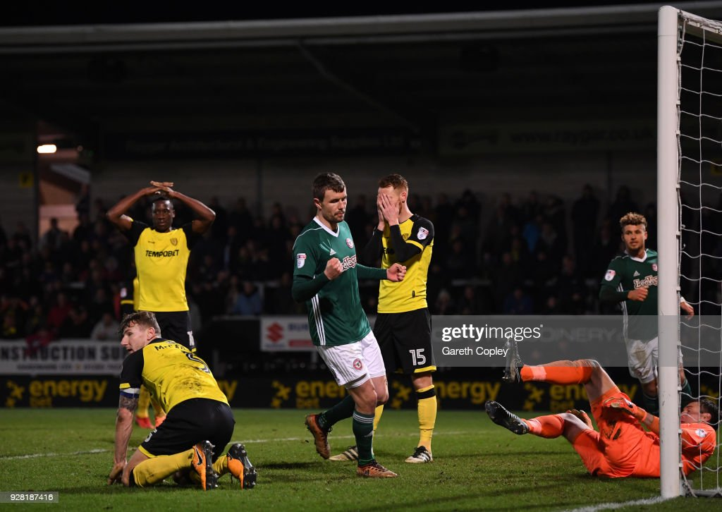 Andreas Bjelland of Brentford celebrates his sides first goal as Kyle McFadzean of Burton Albion (L) scores a own goal during the Sky Bet Championship match between Burton Albion and Brentford at the Pirelli Stadium on March 6, 2018 in Burton-upon-Trent, England.