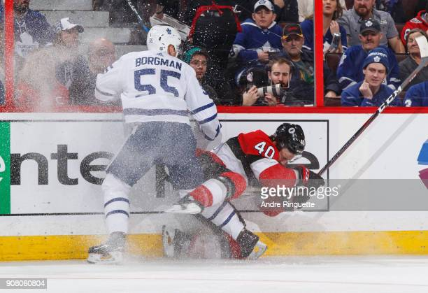 Andreas Borgman of the Toronto Maple Leafs body checks Gabriel Dumont of the Ottawa Senators into the side boards at Canadian Tire Centre on January...