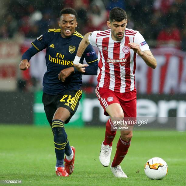 Andreas Bouchalakis of Olympiacos FC attacking and Joe Willock of Arsenal FC during the UEFA Europa League round of 32 first leg match between...
