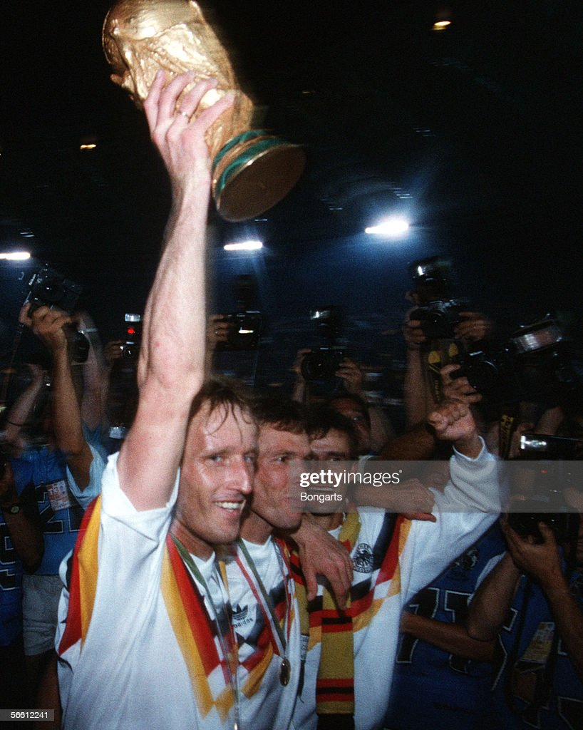 Andreas Brehme (L), Lothar Matthaeus (C) and Pierre Littbarski of Germany celebrates with the trophy after winning the World Cup final match between Argentina and Germany at the Olympic Stadium on July 8, 1990 in Rome, Italy.