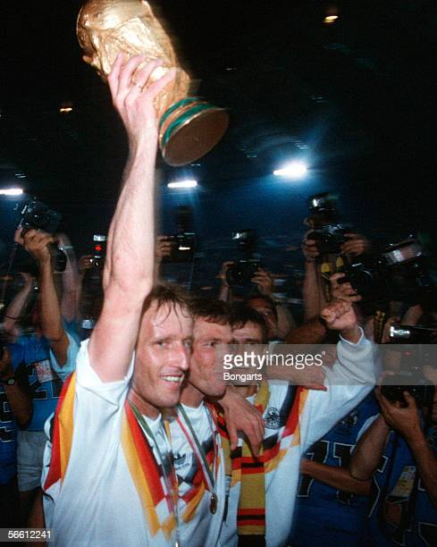 Andreas Brehme Lothar Matthaeus and Pierre Littbarski of Germany celebrates with the trophy after winning the World Cup final match between Argentina...