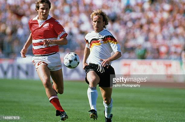 Andreas Brehme of West Germany reaches the ball ahead of Kim Vilfort of Denmark during the UEFA European Championships 1988 Group 1 match between...