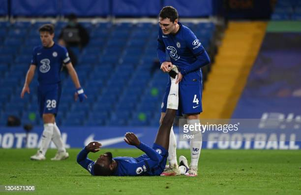 Andreas Christensen of Chelsea helps team mate Antonio Rudiger who looks to be injured during the Premier League match between Chelsea and Manchester...
