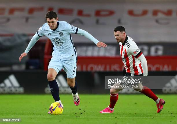 Andreas Christensen of Chelsea runs with the ball as he is closed down by Oliver Burke of Sheffield United during the Premier League match between...