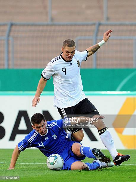 Andreas Drakos Christofides of Cyprus and PierreMichel Lasogga of Germany battle for the ball during the 2013 UEFA European Under21 Qualifier Group 1...
