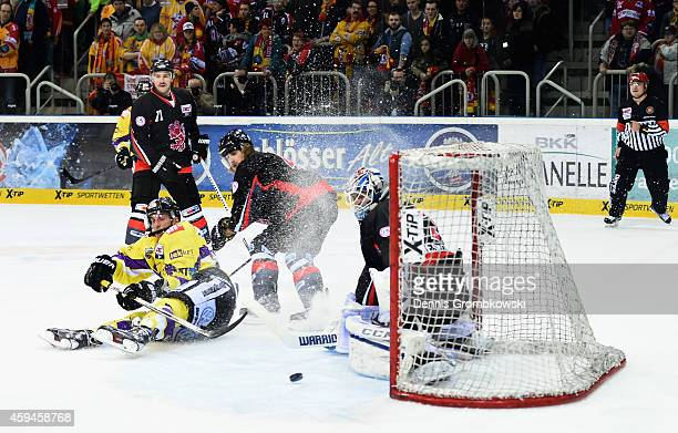 Andreas Driendl of Krefeld Pinguine misses a chance at goal past Tyler Beskorowany of Duesseldorfer EG during the DEL Ice Hockey match between...
