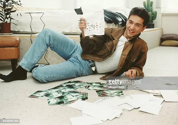 """Andreas Elsholz, Schauspieler aus der Fernsehserie """"Gute Zeiten, schlechte Zeiten"""", liegt vor seinem Bett auf dem Boden und hat seine Autogrammkarten..."""