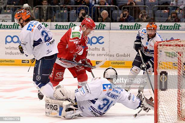 Andreas Falk of Cologne misses a chance at goal under the pressure of goalkeeper Shawn Hunwick and Brandon Rogers of Iserlohn during the DEL match...