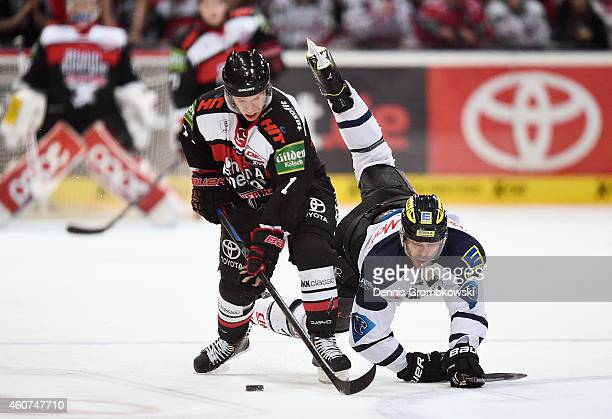 Andreas Falk of Koelner Haie and John Laliberte of ERC Ingolstadt battle for the puck during the DEL Ice Hockey game between Koelner Haie and ERC...