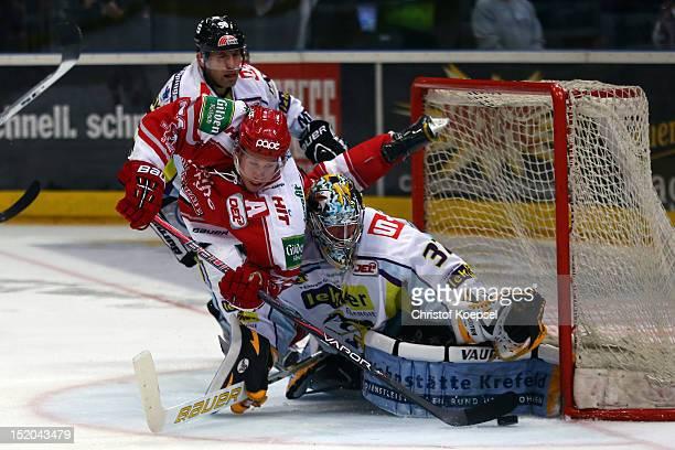 Andreas Falk of Koelner Haie falls over Scott Langkow of Krefeld Pinguine during the DEL match between Koelner Haie and Krefeld Pinguine at Lanxess...