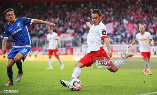 Andreas Geipl of Jahn Regensburg crosses the ball in front of Marvin Mehlem of SV Darmstadt 98 during the Second Bundesliga match between SSV Jahn...