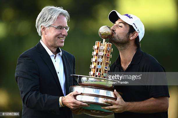 Andreas Haffner poses whilst Alexander Levy of France kisses the trophy after winning in the final round of the Porsche European Open at Golf Resort...
