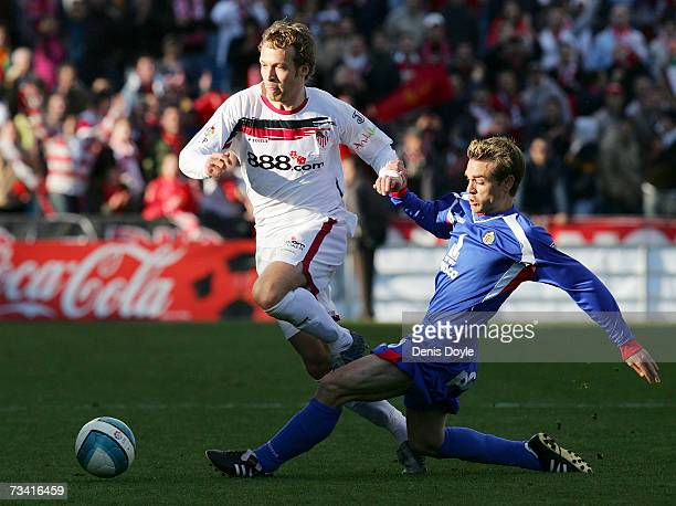 Andreas Hinkel of Sevilla is tackled by Nacho of Getafe in the Primera Liga match between Getafe and Sevilla at the Coliseum Alfonso Perez stadium on...