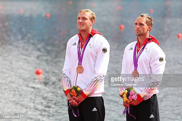 Andreas Ihle and Martin Hollstein of Germany celebrate on the podium after winning Bronze in the Men's Kayak Double 1000m Canoe Sprint final on Day...