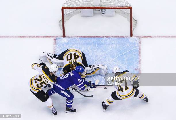 Andreas Johnsson of the Toronto Maple Leafs battles for the puck against Torey Krug of the Boston Bruins and Brandon Carlo in front of Tuukka Rask...