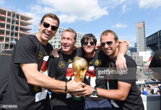Andreas Koepke Joachim Loew Hansi Flick and Oliver Bierhoff celebrate on stage at the German team victory ceremony on July 15 2014 in Berlin Germany...