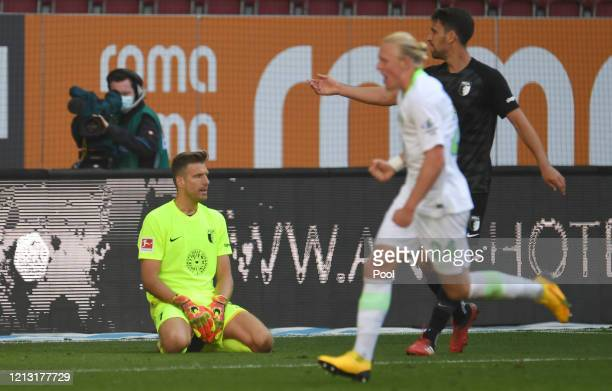 Andreas Luthe of FC Augsburg sits on the grass following the Bundesliga match between FC Augsburg and VfL Wolfsburg at WWK-Arena on May 16, 2020 in...