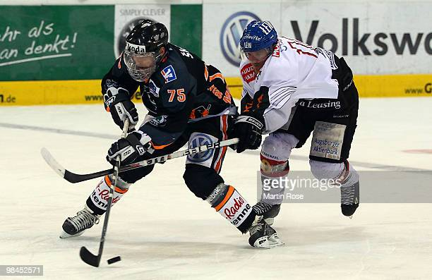 Andreas Morczinietz of Wolfsburg and Rhett Gordon of Augsburg battle for the puck during the third DEL play off semi final match between Grizzly...