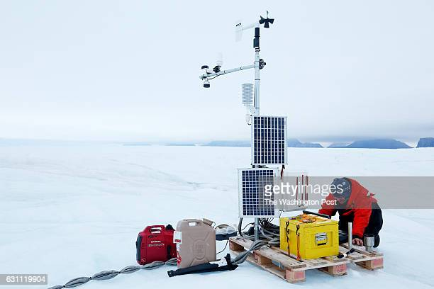 Andreas Muenchow finishes up work on the Automatic Weather Station with a cable that runs deep into the ocean from the surface of Petermann glacier...