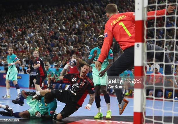 Andreas Nilsson of Veszprem tries to score against Cedric Sorhaindo and goalkeeper Moreno Perez de Vargas of Barcelona during the VELUX EHF FINAL4...