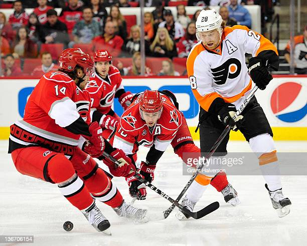 Andreas Nodl and Brandon Sutter of the Carolina Hurricanes knock the puck away from Claude Giroux of the Philadelphia Flyers during play at the RBC...