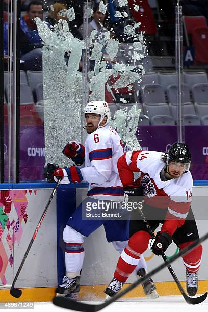 Andreas Nodl of Austria checks Jonas Holos of Norway to break the glass during the Men's Ice Hockey Preliminary Round Group B game on day nine of the...