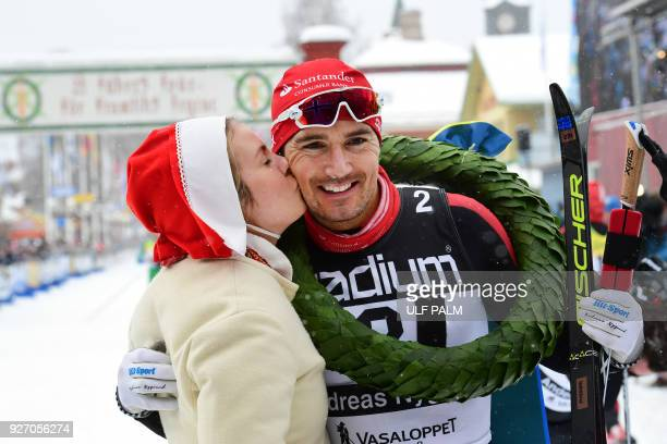 Andreas Nygaard from Norway gets a kiss from kranskulla or wreath girl Sara Wadman after winning the long distance cross country ski competition...