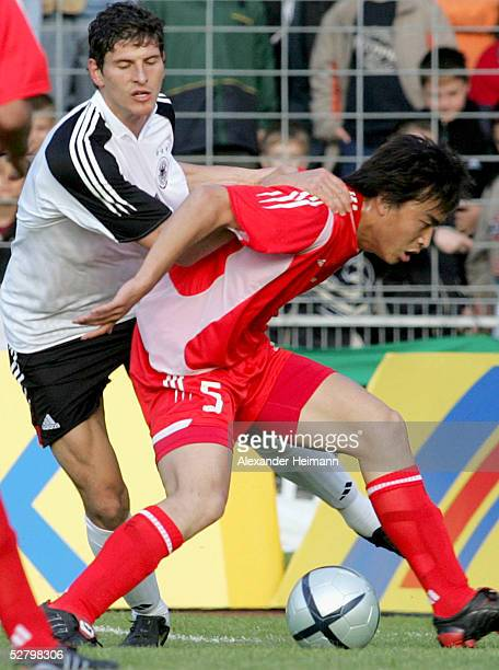 Andreas Ottl of Germany tackles Feng Xiaoting of China during the men's under 20s atch between Germany and China on May 11 2005 in Schweinfurt Germany