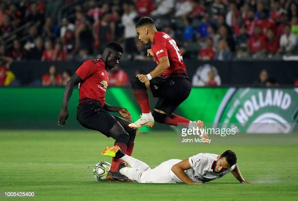 Andreas Pereira of Manchester United jumps over Hakan Calhanoglu of AC Milan in the first half during the International Champions Cup 2018 at StubHub...
