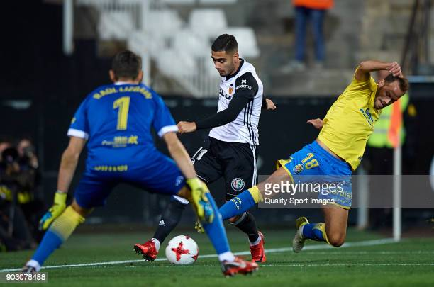 Andreas Pereira of Valencia competes for the ball with Javi Castellano and Raul Lizoain of Las Palmas during the Copa Del Rey 2nd leg match between...