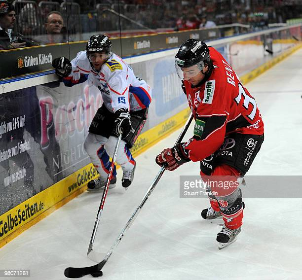 Andreas Renz of Cologne fights for the puck with Pat Kavanagh of Ingolstadt during the DEL playoff match between Koelner Haie and ERC Ingolstadt on...