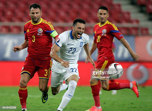 Andreas Samaris of Greece competes with Razvan Rat of Romania during the group F EURO 2016 qualifier between Greece and Romania at Georgios...